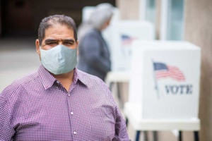 Man in mask at voting station wondering how the 2020 election could affect healthcare